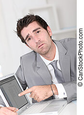 Businessman showing something on laptop computer