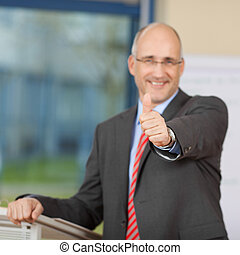 Businessman Showing Thumbs Up Sign At Podium