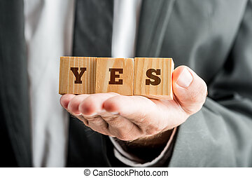 Businessman Showing Wooden Cubes with YES Word