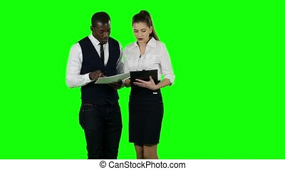 Businessman shows a woman new information. Green screen