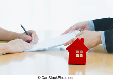 man signing a house insurance policy, the agent is holding the document. concept document sales loan and rental. focust red house on table