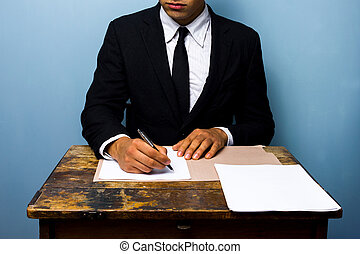 businessman signing documents at old wooden desk