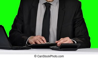 Businessman signing documents on reflective table. Green screen