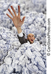 Businessman sinking in big heap of crumpled papers