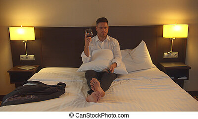 Businessman sit on bed with glass of wine and watch TV in room of the hotel