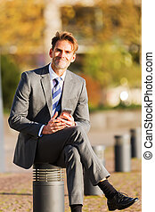 businessman sits on a post with a cellphone