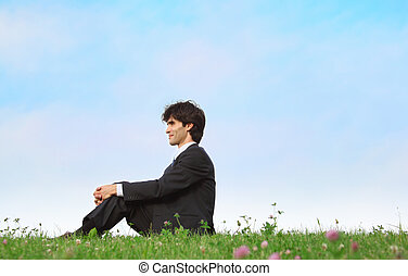 businessman sits on grass, view in profile