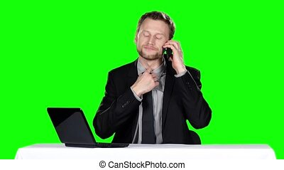 Businessman sitting and talking on the phone. Green screen -...