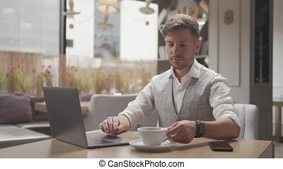 Businessman sitting and working in a cafe. Man using computer devices. Business and entrepreneurship.