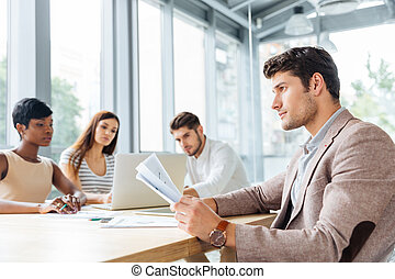 Businessman sitting and working with his business team in office
