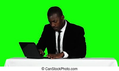 Businessman sitting at a desk and using laptop. Office work. Green screen