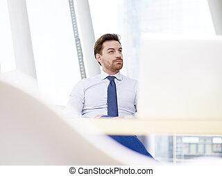 businessman sitting at desk thinking