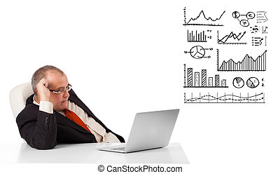 businessman sitting at desk with graphs and laptop