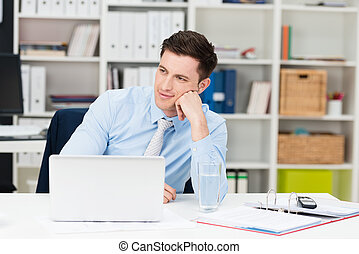 Businessman sitting at his desk daydreaming