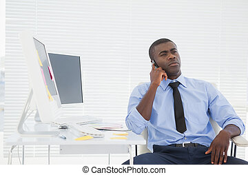 Businessman sitting at his desk on the phone in his office