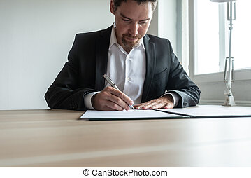 Businessman sitting at his desk signing a document