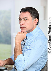 Businessman sitting at his desk with hand on chin