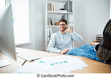 Businessman sitting at his workplace and talking on mobile phone