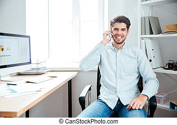 Businessman sitting at his workplace in office with mobile phone
