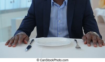 Businessman sitting at table in restaurant.