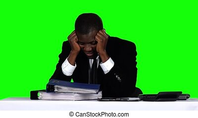 Businessman sitting at the table and holding his head. Green screen