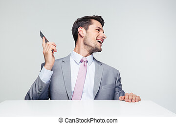 Businessman sitting at the table with smartphone