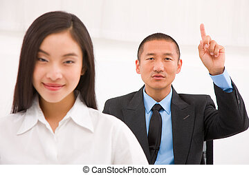 Businessman sitting behind businesswoman raising his finger