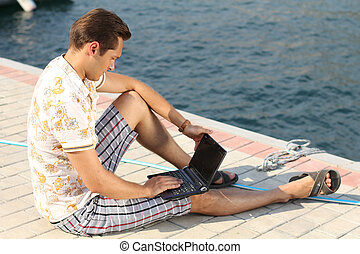 businessman sitting by the sea with a laptop