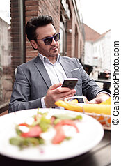 businessman sitting in a street cafe