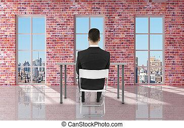 businessman sitting in brick room