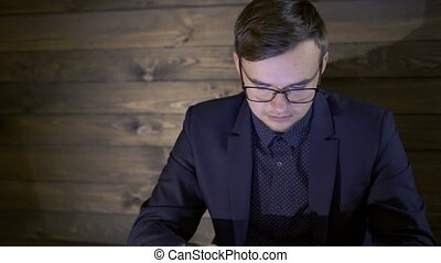 Businessman sitting in cafe, thinking and using the laptop