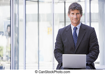 Businessman sitting in office lobby using laptop smiling
