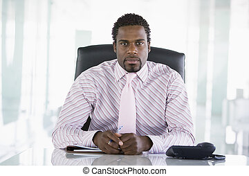 Businessman sitting in office with personal organizer