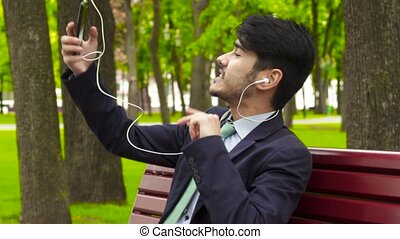Businessman sitting in park and eating french fry during his...