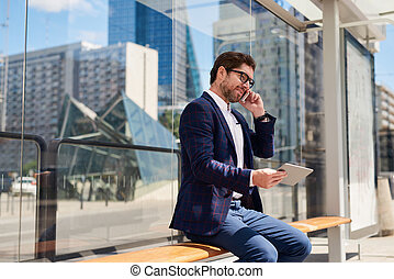 Businessman sitting in the city using a cellphone and tablet