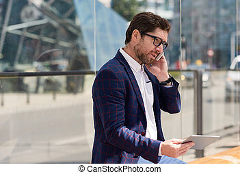 Businessman sitting in the city using a tablet and cellphone