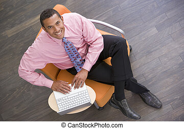Businessman sitting indoors with laptop smiling