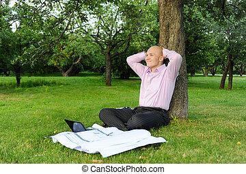 Businessman sitting near a tree - Businessman with laptop ...