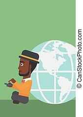 Businessman sitting near Earth globe.
