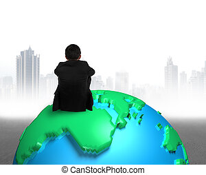 businessman sitting on 3d map globe watching gray buildings city
