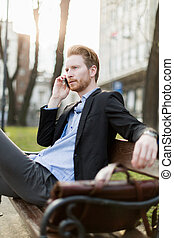 Businessman sitting on a  bench  and talking on the phone on a sunny day