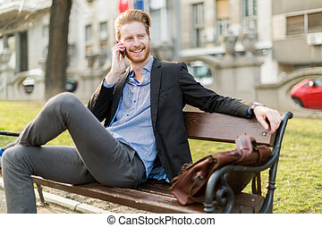 Businessman sitting on a park bench while talking on the phone on a sunny day and smiling