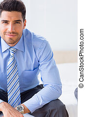 Businessman sitting on bed smiling at camera at home in...