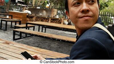 Businessman sitting on bench at outdoor cafe 4k - Young...