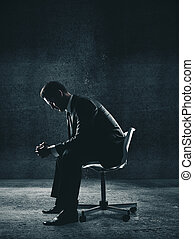 Businessman sitting on chair in concrete room.