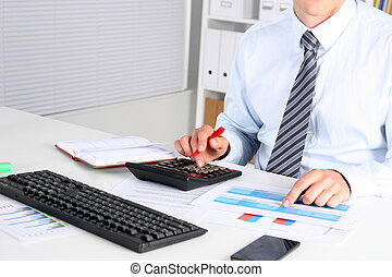 Businessman sitting on desk and writing a paper