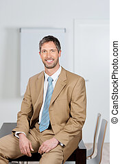 Businessman Sitting On Desk In Office