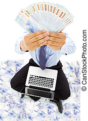 businessman sitting on floor and showing the money