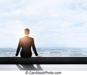 businessman sitting on roof