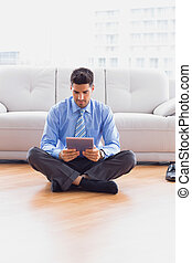 Businessman sitting on the floor using tablet